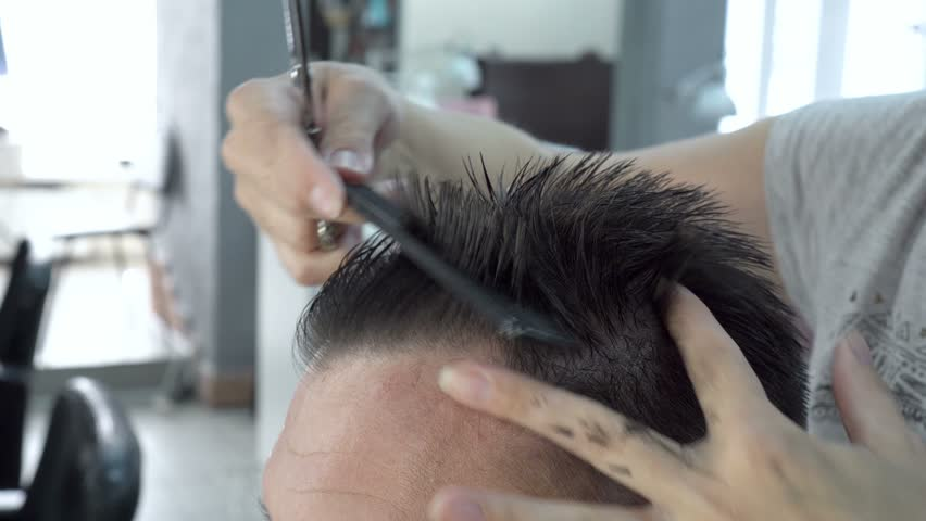 Professional the Barber cuts the man's hair in Barber shop. The woman collects the tips of her hair between her fingers and cuts them with scissors. Hair care. Close-up. 4K, 25 fps.