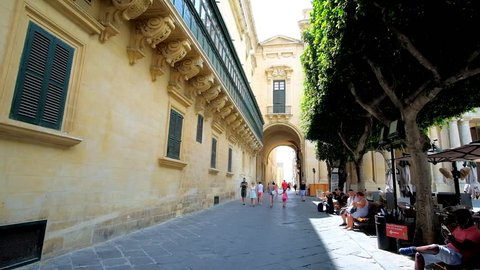 VALLETTA, MALTA - JUNE 17, 2018: The Old Theatre street stretches along the side wall of Grandmaster's Palace and trimmed trees of Republic Square with a view on Palace arch, on June 17 in Valletta.