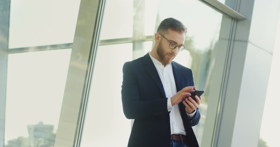 Attractive young businessman wearing in official style clothing standing in a sunlight and typing or scrolling on his smartphone.