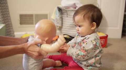 Baby Sitting and Kissing Doll on Floor