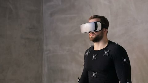 Indoor portrait handsome brunette man talking using vr glasses and motion  capture suit for online playing video game entertainment industry virtual  reality headset digital sensors technology business