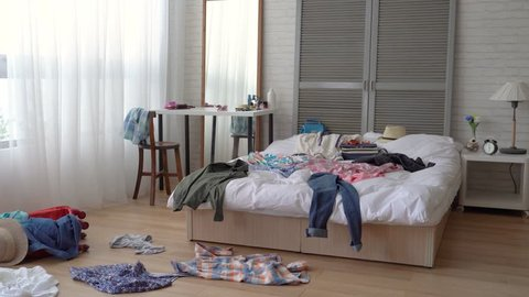 The scene of a messy girl bedroom. Clothes scattered everywhere. Housekeeper is lazy to clean them up.