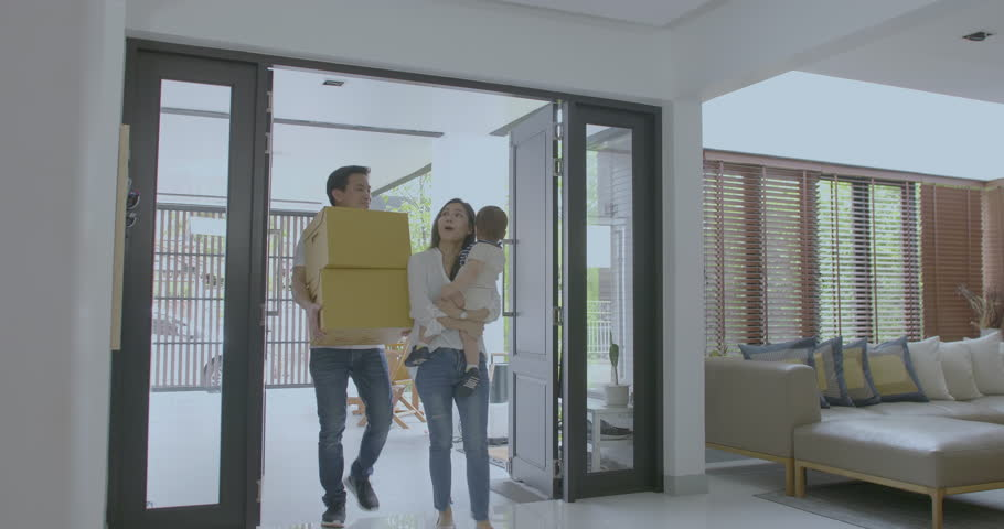 Happy family with kids holding boxes entering new modern house, family relocating concept
