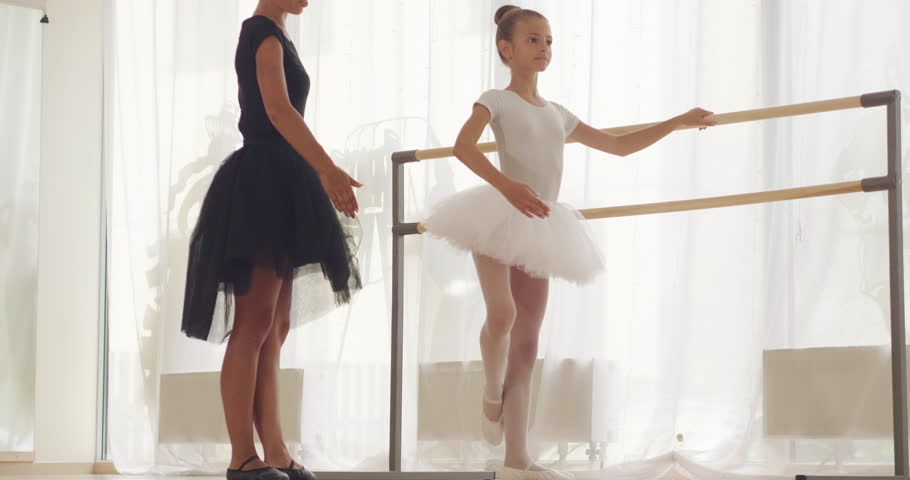 A teacher of classical dance teaches some steps to his young student who wants to learn how to dance. Concept of: ambition, education, teaching and love for the dance | Shutterstock HD Video #1014795509