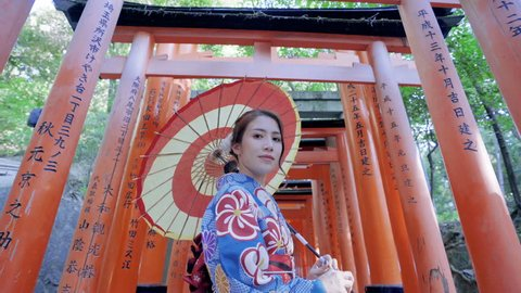 Asian women in traditional japanese kimonos is smiling and happiness at Fushimi Inari Shrine in Kyoto, Japan.