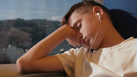 The boy is sleeping by the window in the train car. The boy is traveling the world. Tourist boy on the train