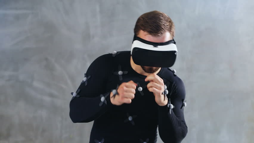 986a1828e3ce brunette athletic man in motion capture suit using virtual reality headset  boxing playing video-game online freelance animator developer film movie ...
