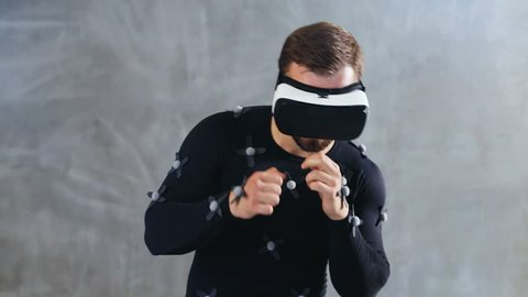 Brunette athletic man in motion capture suit using virtual reality headset  boxing playing video-game online freelance animator developer film movie  production business futuristic technology innovation
