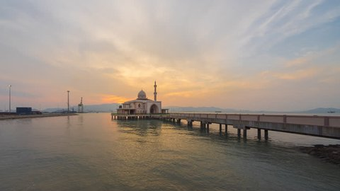 Beautiful sunset time lapse of a floating mosque at the end of a jetty at a port in Malaysia at dusk from day to night. Prores Full HD 1080p.