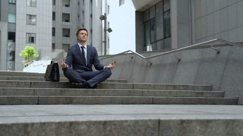 Calm businessman sitting in lotus position, self-control in stressful life