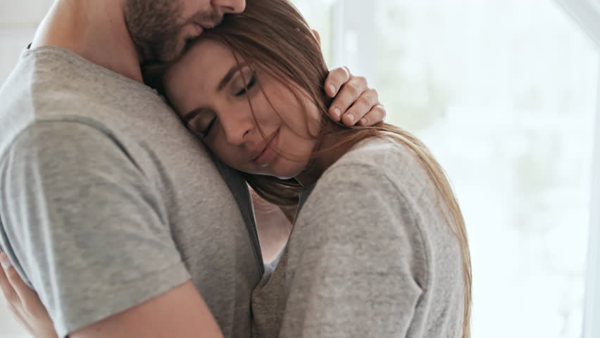 Handheld medium shot of happy young woman smiling and resting her head on chest of bearded man in sleepwear hugging her and stroking her hair