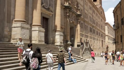 Salamanca, Spain - August 2018: Tourists pass along Calle Compania past the columned facade of the Pontifical University