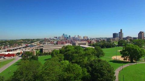 Slow drone flight over trees to reveal the Kansas City skyline.