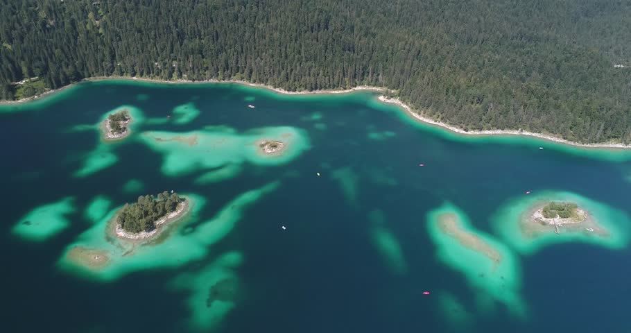 Eibsee, Bavaria, Germany - Flying over the beautiful islands of the famous Eibsee on this beautiful summer day. Lots of tourists swimming and paddling. #1014903859