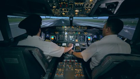 Male pilot is helping his trainee to control the plane simulator. Modern passenger airplane cabin interior.