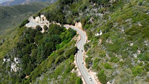 Aerial Shot Descending Over and Flying Towards a Group of Cars Traveling Along the Side of a Mountain Road near Lake Arrowhead, California