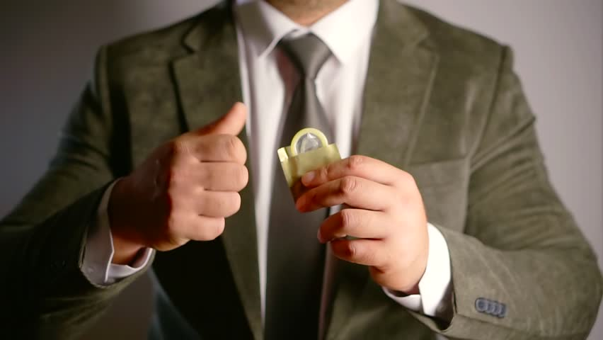adult man dressed in expensive jacket is unpacking a condom and showing it to camera, close-up