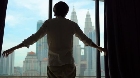 Superslowmotion shot of a silhouette of a successful rich man opening the curtains of a window overlooking the city center with skyscrapers