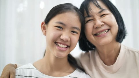 4K 60fps : Close up smiling face of happy Asian girl hugging her grand mother, Multi generation of Asian female
