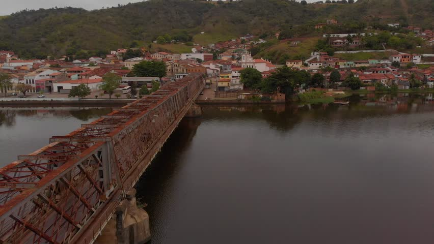 Drone shot of cars on rusty iron bridge in River Paraguaçu in Cachoeira, Bahia, Brazil with church and city on the background.
