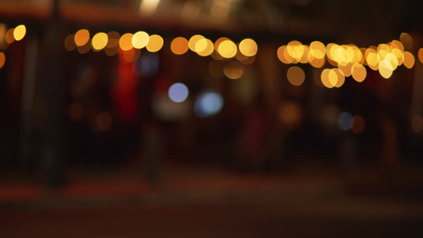 Out of focus background plate of city street with bokeh lights shot from sidewalk of downtown urban area. Blurry Video backdrop for green screen compositing. 4k