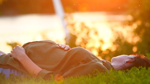 Pregnant Woman lying on green grass, looking on river, touching her Belly and dreaming. Healthy Pregnancy. Pregnant tummy. Expectant female outdoor in summer park on sunset. Slow motion 4K UHD video