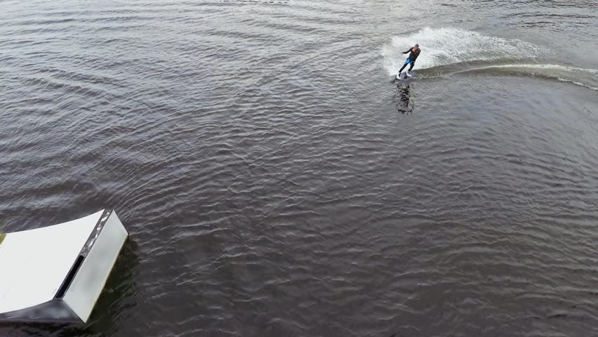 Handsome guy in a wetsuit is riding a wakeboard on the river | Shutterstock HD Video #1015067329