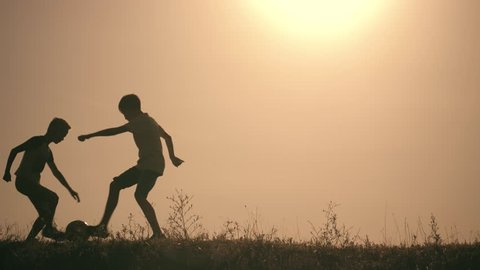 Two boys playing soccer at sunset. Silhouette of children playing with a ball at sunset. The concept of a happy family