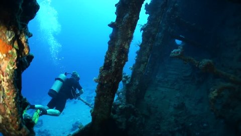 Looking out of bow section of wreck of the Carnatic in the Red Sea to diver who swims round and looks in through the bowsprit hole.