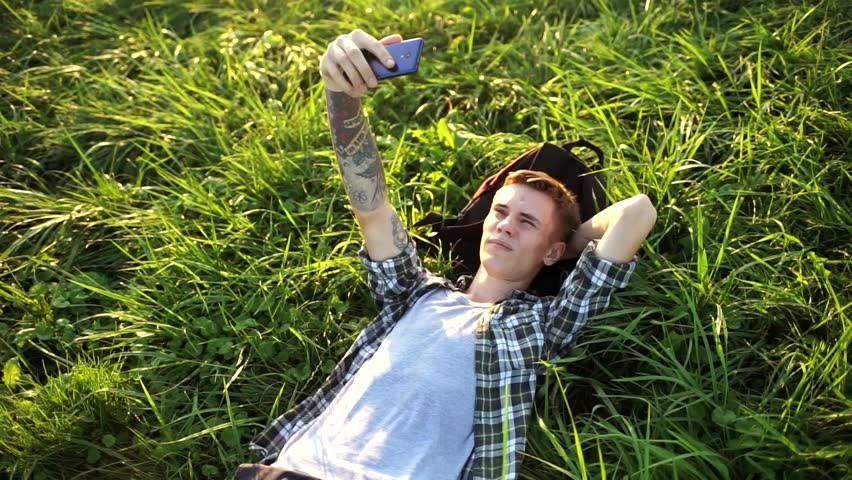A handsome guy is lying on the grass and talking on video. The student is lying on the grass and talking on the phone. A young man smiles and takes a selfie. Nice guy lying on the grass with his phone   Shutterstock HD Video #1015092589
