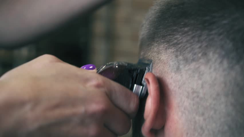 Close-up view on male's hairstyling in a barber shop with professional trimmer. Man's haircutting at hair salon with electric clipper. Grooming the hair. Slow motion