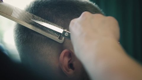 Attractive male is getting a modern haircut in barber shop. Barber cutting hair with scissors and comb in male hair salon