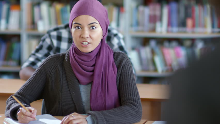 Tilt down of young muslim woman in hijab writing in notebook at desk and speaking with teacher at lesson