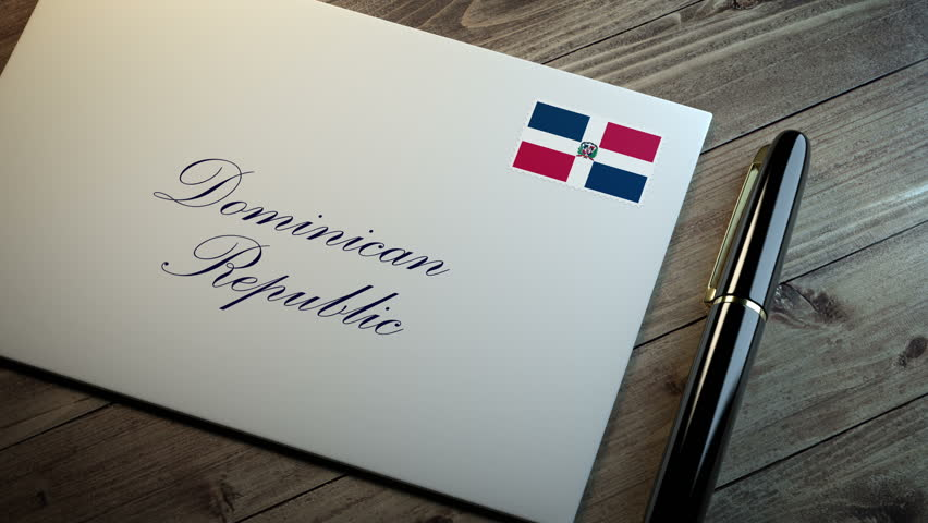 Country name written on a card or envelope in cursive font with a sleek pen on a wooden table surface under beautiful classy light. Stamp in the corner shows the flag of Dominican Republic