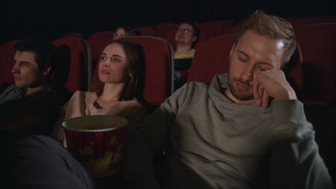 Man sleep at cinema movie. Guy sleeping at cinema date. Guy fall asleep at movie theatre. Bored man sitting at movie hall. People watching boring film