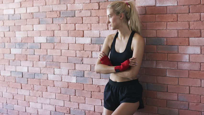 Lovely young female in black sportswear keeping arms crossed and looking at camera while leaning on brick wall in gym | Shutterstock HD Video #1015179589