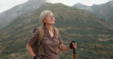 Mature caucasian woman hiking in mountains with backpack, enjoying her adventure - tourism concept closeup 4k