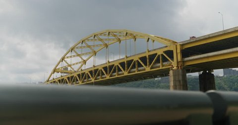 A daytime dolly up establishing shot of the iconic yellow Fort Duquesne Bridge over the Allegheny River in downtown Pittsburgh, Pennsylvania on an overcast summer day.