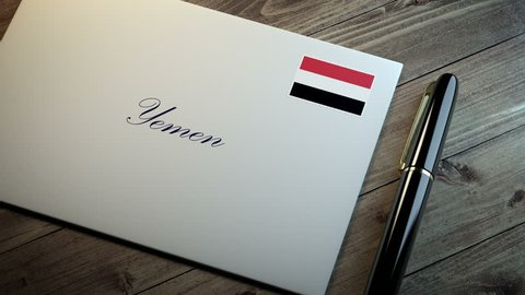 Country name written on a card or envelope in cursive font with a sleek pen on a wooden table surface under beautiful classy light. Stamp in the corner shows the flag of Yemen