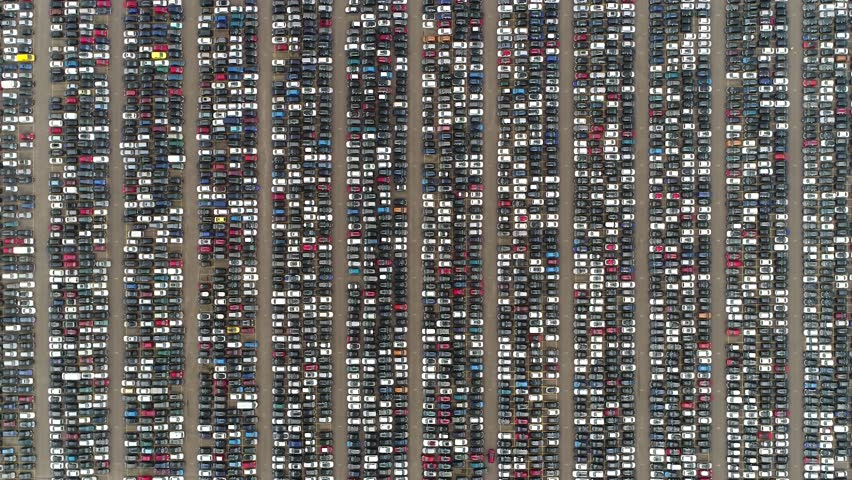 Aerial top down view of automaker car lot showing vehicles parked close to each other ready for further distribution the automotive industry is one of worlds most important economic sectors by revenue | Shutterstock HD Video #1015207909