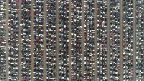 Aerial top down view of automaker car lot showing vehicles parked close to each other ready for further distribution the automotive industry is one of worlds most important economic sectors by revenue