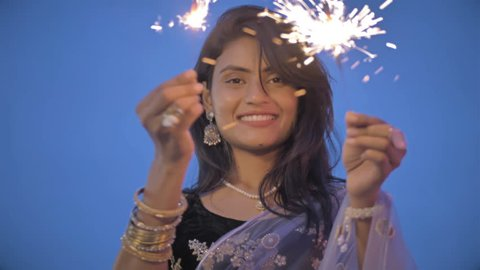 An Young and beautiful woman in a traditional sari playing with fire sparkle or fire cracker. Slow motion shot of an attractive and smiling lady playing with fireworks outdoors during Diwali Festival