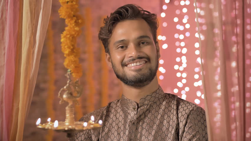 A happy young man smiling next to a hanging oil lamp in traditional cloths during Diwali festival. A handsome man wearing kurta smiles in a warm interior house decorated with lights and flowers