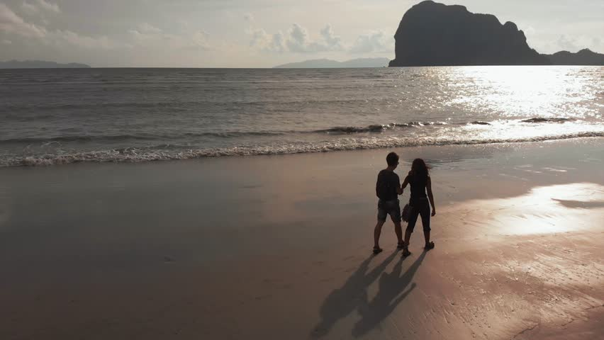 Young romantic couple walking on beach. Sun Flares. Couple exploring the beach. Romantic happy young couple enjoying ocean sunset during travel