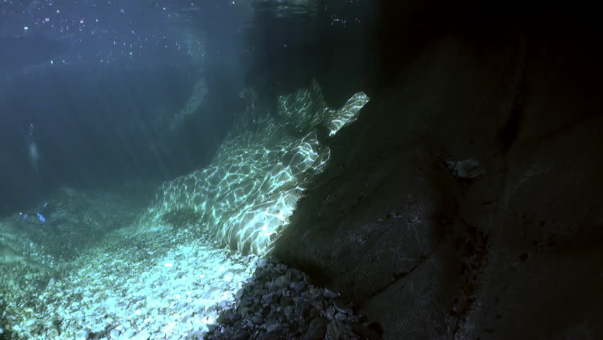 Camera operator in refraction of sunlight underwater in transparent river. Shooting a frame of picturesque nature on background of huge smooth stones in Verzasca. | Shutterstock HD Video #1015244179