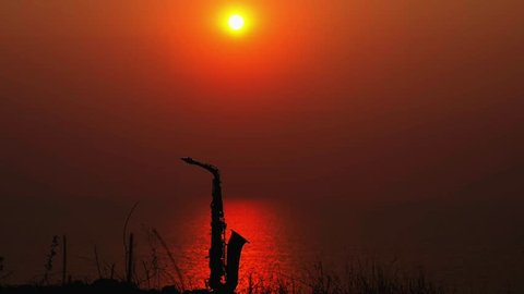 Silhouette of alto saxophone against the background of orange sunset and sea