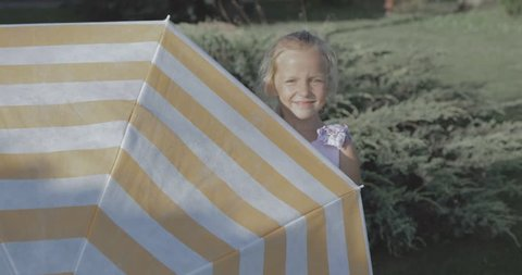 Cute girl with umbrella having fun on grass and laughing. Pretty kid hides behind a parasol. 4k video shooting by handheld gimbal