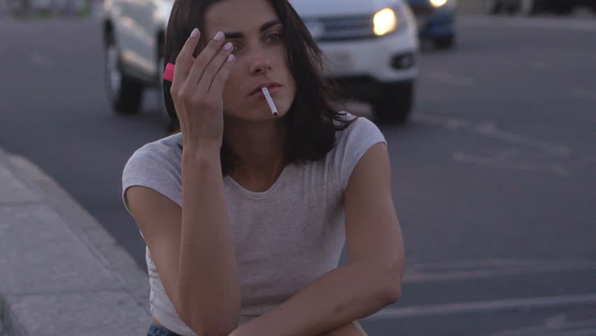 young gray-haired sexy brunette smokes a cigarette. A woman sits on the side of the road and throws a bull to the ground. Warm summer evening