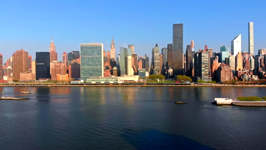 Aerial Drone Footage panning left of New York City Manhattan skyline over East River viewed from Gantry Plaza State Park in Long Island City