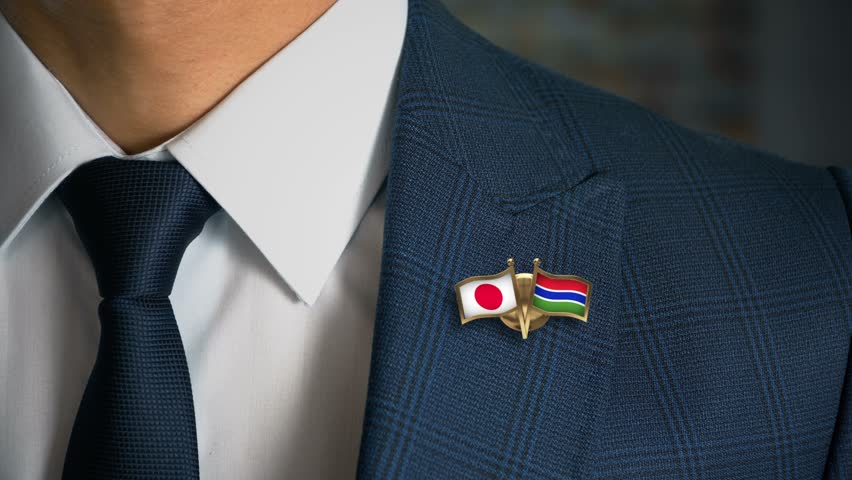 Businessman Walking Towards Camera With Friend Country Flags Pin Japan - Gambia